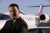 Businessman standing near a airplane, portrait.