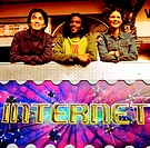 Group of three young people standing outside an internet cafe