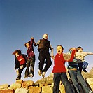 Low angle view of children (6-10) holding hands and jumping off rocks