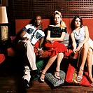Portrait of three young people sitting on a couch holding martini glasses