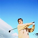 Low angle view of a young man playing golf