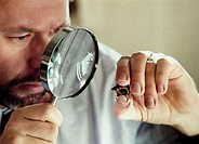 Man looking at a signet-ring through a magnifying glass