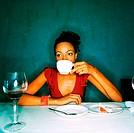 Young woman sitting at a table drinking coffee