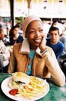 A teenage girl sitting at table with burger and french fries and group of teenagers (14-16) behind her