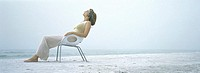 Woman sitting in chair on beach, wearing headphones