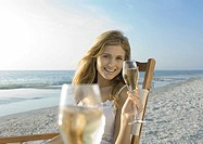 Young woman drinking champagne on beach