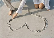 Woman drawing heart in sand on beach, partial view