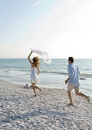 Newlyweds, man chasing woman on beach