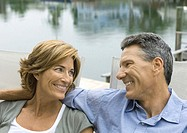 Mature couple sitting near water, smiling at each other