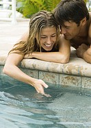 Young couple lying by edge of pool, woman dipping hand into water