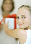 Girl holding out present to woman, smiling over shoulder at camera