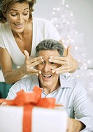 Woman surprising husband with christmas present