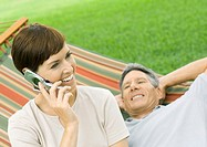 Woman using cell phone while man lounges on hammock