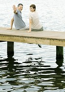 Couple sitting on dock, man waving at camera