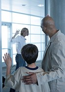 Woman waving goodbye to man and boy in airport