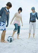 Three young adult friends playing soccer on beach