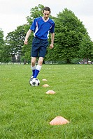 Footballer dribbling ball