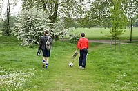 Two young men in park with football