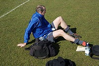 Footballer sitting on grass