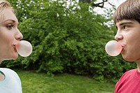 Teenage couple blowing bubble gum bubbles