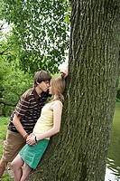 Teenage couple kissing near tree (thumbnail)