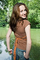 Smiling girl standing near a lake