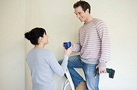 Woman handing coffee to husband on step ladder