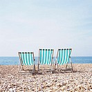 Three deckchairs on a shingle beach (thumbnail)