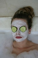 A woman relaxing in bathtub with cucumber slices on her eyes.