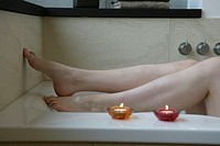 A woman bathing in her bathtub with two candles at her side.
