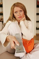 A woman watching television with a remote control in her hand.