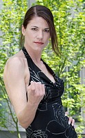 A woman wearing a trendy black dress looks at the camera.