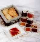 Bread in basket, marmalade in jars, slice of bread with jam on plate