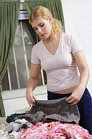 Caucasian woman in her 20's folding man's underwear