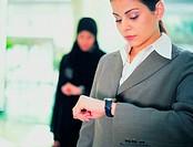 Arab businesswomen checking time
