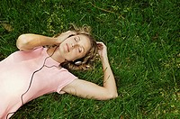 Woman Reclining on Grass Listening to Music on Headphones