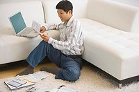 Man Seated on Floor Paying Bills