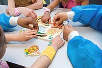 Children and nurses playing with puzzle
