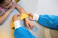 Girl watching nurse put bandage on her arm
