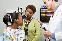 Doctor reassuring mother and daughter