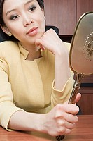 Businesswoman looking at mirror
