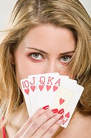 Woman covering face with cards