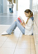 Girl sitting on floor in school hallway, leaning against lockers and studying