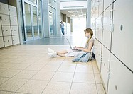 Teenage girl sitting on floor, leaning against lockers, using laptop, teenage boy standing in distance