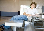 Teenage boy sitting on bleachers in school gym, studying