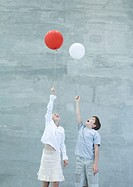 Two children holding helium balloons