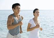 Couple running next to ocean