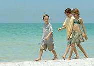 Three children walking next to surf on beach
