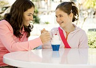 Two preteen girls sharing dessert