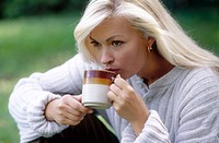 woman drinking coffee/tea outdoors